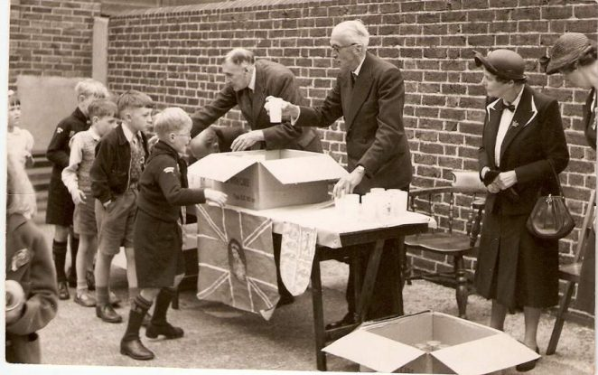 The picture is taken in the playground of St Mary's School and the Coronation mugs are being handed out by, I believe, School Governors. I only recognise me, the second boy in the line just about to get a mug, which I still have today. | From the private collection of Dennis Parrett