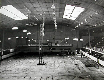 Sports Stadium Interior. This is the only known photograph of the Sports Stadium interior the day after its closure in October 1965. The previous week had seen the Conservative Party hold their annual conference at the rink.The remaining rink staff can be seen dismantling the huge floodlights from the high roof in preparation for the demolition of the rink. The ice is still there under the floor covering and eventually has to be drained by cutting large channels in the ice to allow it to melt. The next task would be to dismantle miles of copper piping used to freeze the saline solution used for the ice rink. Under the copper piping still remains the original scaffolding and floor that was built over thirty years ago in 1935, when the Swimming Stadium was turned into an ice rink. Under this remains the original swimming pool with portholes (see other images of the demolition under West St) and remains virtually unscathed! The final stage of the demolition was completed in the January of 1966, the
