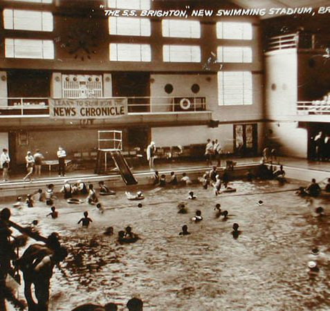 This original photograph postcard shows the interior of Swimming Stadium Brighton in 1934/5. The ship (Queen Mary) resting on the first floor deck was anchored in the middle of the pool at the end of the day and floodlit.