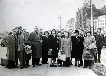 Brighton Tigers Supporters Club: This photograph was taken on Brighton promenade (opposite the Grand Hotel) and shows the Brighton Tigers ice hockey supporters club awaiting transport. The twenty-one members of the club were to make history as one of the first supporters clubs to fly to an away match in 1948. The group includes Mr FA Knowles the Brighton Sports Stadium manager and to the left with the megaphone, Mr Charlie Connell. Charlie was the cheerleader of the Tigers and could be seen at every match encouraging the supporters to urge their team on to greater heights. Familiar in his straw boater and club scarf, Charlie would shout encouragement to the crowd through a large megaphone much to their delight.   From the private collection of Trevor Chepstow
