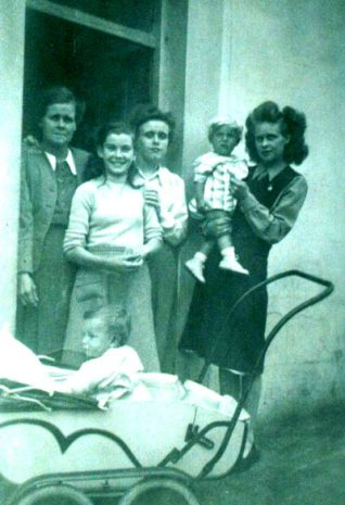 The Bailey Family at 15 Regent Hill Brighton. The photograph shows the famous pram with my son Trevor sitting in it.  From left to right is my Mother Angnes, Evelyn, me, Kathleen and my sister Dorothy holding her son Michael. | From the private collection of Mrs Kathleen A. Kis (nee Bailey)
