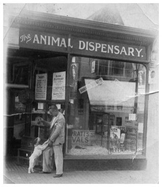 Dad and canine friend outside the shop. Click on the image to open a large version in a new window. Click on image again to enlarge | From the private collection of Tony Hill