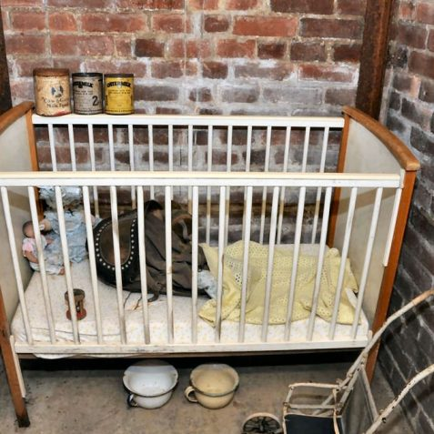 A 1940s Childs cot and pushchair - the black object in the cot is a baby's gas mask | Photo by Tony Mould