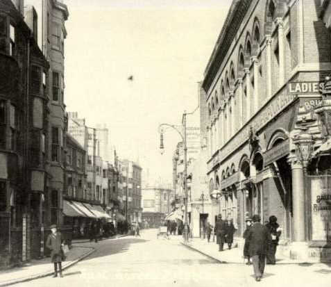 East Street, c. 1907: East Street looking north in about 1907. On the right is the Clarendon Buffet and Hotel Bristol Restaurant. Next to this is Brill's Vapour Baths with a special entrance for the ladies. On the left is Cutler and Co. Ladies Hairdresser, Fuller's Tea Rooms and the Brighton School for Embroidery. | Image reproduced with kind permission from Brighton and Hove in Pictures by Brighton and Hove City Council