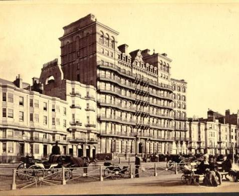 The Grand Hotel, c. 1900: Photograph of the seafront showing The Grand Hotel with horse-drawn carriages and people in period costume in the foreground. | Image reproduced with kind permission from Brighton and Hove in Pictures by Brighton and Hove City Council