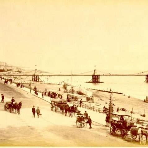 Promenade near Chain Pier, c. 1890: A busy scene on the beach near the Chain Pier, with bathing machines and electric tram on the beach. | Image reproduced with kind permission from Brighton and Hove in Pictures by Brighton and Hove City Council