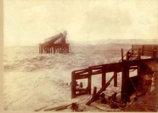 Remains of Chain Pier, 1896:  Ruins of the Chain Pier after the storms of 1896. Palace Pier under construction in the background. | Image reproduced with kind permission from Brighton and Hove in Pictures by Brighton and Hove City Council