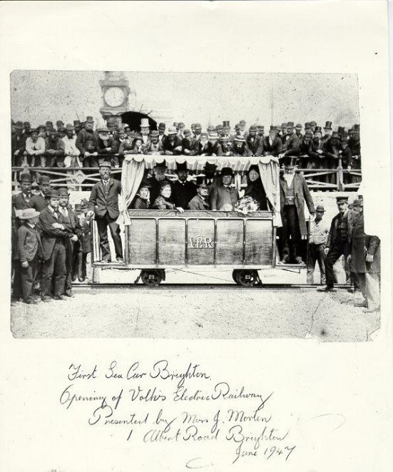 The opening of Volk's Electric Railway at 12 noon, Saturday 4th August, 1883. Magnus Volk, wearing a peaked cap, is standing on the left footboard. The Mayor of Brighton stands on the right footboard. Anna Banfield, wife of Magnus Volk is seated on the left inside the car. Several hundred onlookers witnessed the first voyage which took place a few minutes after this photograph was taken. | Image reproduced with kind permission from Brighton and Hove in Pictures by Brighton and Hove City Council