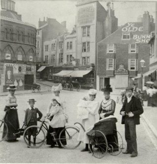 Group of men, women and children with bicycles in Pool Valley. 18th Century Bun Shop and clock factory in the background. | Image reproduced with kind permission from Brighton and Hove in Pictures by Brighton and Hove City Council