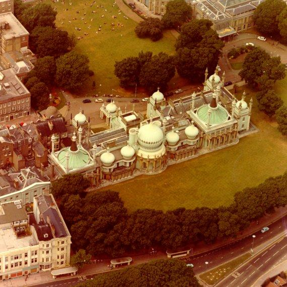 Aerial view of the Royal Pavilion Estate before work was started on its restoration. Note the road and parking spaces in front of the Pavilion. c.1965 | Image reproduced with kind permission from Brighton and Hove in Pictures by Brighton and Hove City Council