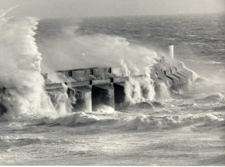 Storm at Brighton Marina, 1988: Stormy sea breaking over the Marina sea wall. Photograph Copyright Evening Argus.   Image reproduced with kind permission from Brighton and Hove in Pictures by Brighton and Hove City Council