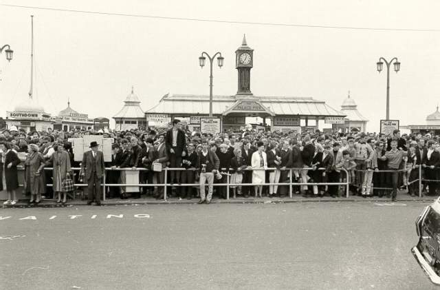 Mods and Rockers at Palace Pier, c. 1964: Crowds of Mods, Rockers and other pedestrians on the pavement outside the entrance to Palace Pier. Four people are attempting to cross the road. | Image reproduced with kind permission from Newsquest Ltd