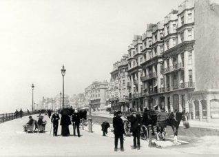 King's Road and Queen's Hotel, c. 1890: King's Road c. 1890 looking west past Queen's hotel. In foreground is a horse cab, railings, seats and street lights are prominent. | Image reproduced with kind permission from Brighton and Hove in Pictures by Brighton and Hove City Council