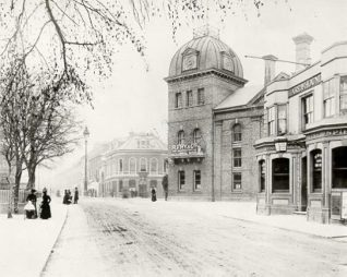 Longhurst's Amber Ale Brewery at Preston Circus, c. 1890. Winter scene of Preston Circus in 1890's showing Longhurst's Amber ale breweries (built 1881) and Hare and Hounds Public House. The Brewery has been taken over by R. Fry and Co. to produce mineral water. In background is Stamford Arms Public House. | Image reproduced with kind permission from Brighton and Hove in Pictures by Brighton and Hove City Council