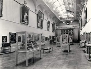 Main Gallery, Brighton Museum, c. 1965: Main gallery of Brighton Museum display cases share the space with the works of art. | Image reproduced with kind permission from Brighton and Hove in Pictures by Brighton and Hove City Council