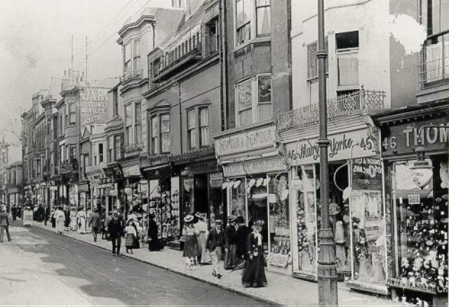 Edwardian view of Western Road shops c. 1900 (southern side) looking east from No. 46. The shops have plate glass windows and exterior gas lighting to illuminate them at night. | Image reproduced with kind permission from Brighton and Hove in Pictures by Brighton and Hove City Council