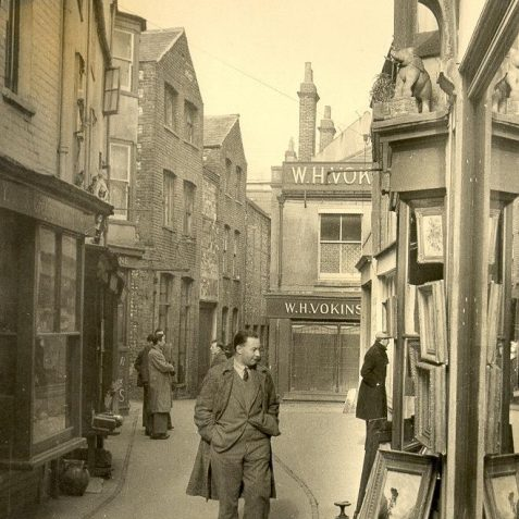 In The Lanes, c. 1940: Gentleman about to enter a picture shop in The Lanes. Vokins department store in the background. | Image reproduced with kind permission from Brighton and Hove in Pictures by Brighton and Hove City Council