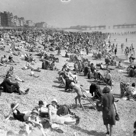 Brighton beach, packed with holiday makers during the spring of 1940, the beach was closed to the public in June 140 when work on anti-invasion defences began. Palace Pier can be seen in the background, a section of the walkway has already been removed to prevent the pier being used to land troops; the beach was soon blocked with obstacles and mines as part of the anti-invasion defences. | Image reproduced with kind permission from Brighton and Hove in Pictures by Brighton and Hove City Council