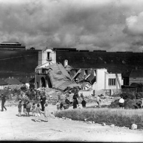 On 16th August 1943 St. Cuthman's Church, which had been built in Lintott Avenue in 1937, was destroyed by a German bomb. A church warden was buried alive. This photograph shows the people looking at the ruins, with Brighton racecourse in the background. The new church was built during 1951-2. | Image reproduced with kind permission from Brighton and Hove in Pictures by Brighton and Hove City Council