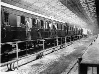 Painting Carriages at Brighton Railway Works, 1928: A team of men painting carriages by hand at the Brighton railway paint shop. The paint shop was built in 1878 to the north of Old Shoreham Road, and soon after this photograph was converted into an electric stock maintenance centre. | Image reproduced with kind permission from Brighton and Hove in Pictures by Brighton and Hove City Council