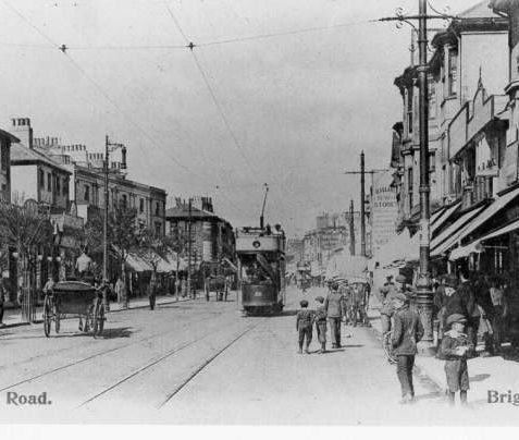 London Road Looking North, c. 1910: A view of London Road, showing canopied shopfronts and tram lines running along the centre of the road. A group of children and adults appear to be waiting for the approaching tram. | Image reproduced with kind permission from Brighton and Hove in Pictures by Brighton and Hove City Council