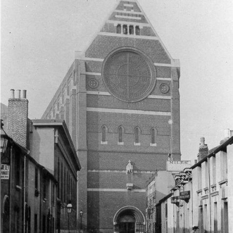 Exterior of St. Bartholomew's Church, c. 1905: St. Bartholomew's Church was built for the Revd. Arthur Wagner by the architect Edmund Scott between 1872-74. It opened in 8 September 1874, became a parish church in July 1881 and was consecrated on 15 June 1887. It was built in Italian Gothic style with a large rose window, below which there was a statue of St. Bartholomew. Supposedly built to the dimensions of Noah's Ark, 180 feet long, 140 feet high and 58 feet long, it is a prominent feature of the Brighton skyline | Image reproduced with kind permission from Brighton and Hove in Pictures by Brighton and Hove City Council