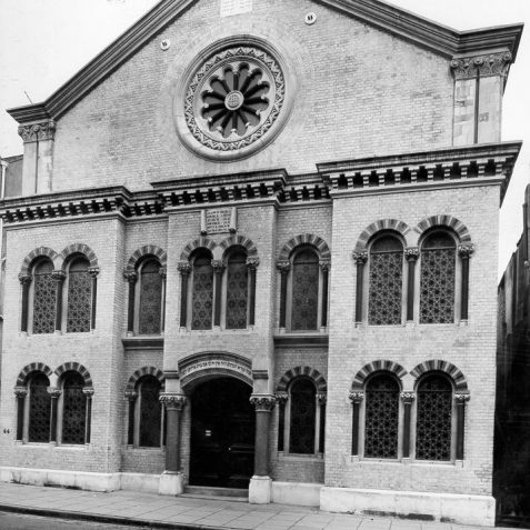 Exterior of Brighton Synagogue, c. 1960s: Brighton Synagogue was built in 1874-5 by Thomas Lainson in Byzantine style. It was consecrated on 23 September 1875 and further improved until 1914 by funds from the Sassoon family. This yellow-brick building is listed and has a very large pediment with Composite pilasters and Corinthian columns on its doors and windows. Copyright of Brighton and Hove Synagogue. | Image reproduced with kind permission from Brighton and Hove in Pictures by Brighton and Hove City Council