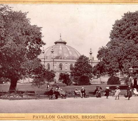 Pavilion Gardens, c. 1910: Men, women and children sitting and promenading in the Pavilion Gardens. The Dome is in the background. | Image reproduced with kind permission from Brighton and Hove in Pictures by Brighton and Hove City Council
