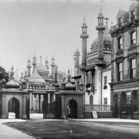South Gate and Pavilion Buildings; built in 1851 to replace the original gate of 1831. There are two Mughal archways with cast iron umbrella-shaped domes (known as chattris) and a low iron gate between them. They were demolished in 1921 and replaced by the current Indian gateway. | Image reproduced with kind permission from Brighton and Hove in Pictures by Brighton and Hove City Council