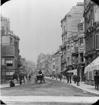 West Street looking North c1900. On the right is the Grand roller skating rink, which later became successively a 2000 seat cinema, Sherry's Dance Hall, a roller skating rink again, then the Ritz amusement arcade in the 1960s. The facade of the building was demolished in 1969 and remodelled as a night-club and amusement arcade. | Reproduced courtesy of  Royal Pavilion, Libraries & Museums, Brighton & Hove
