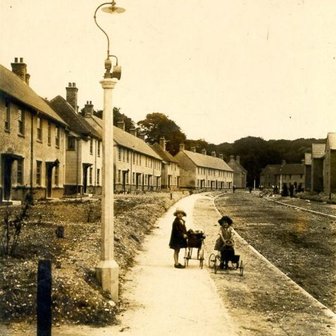 North Moulsecoomb Housing Estate, c. 1926-30: Children playing with a dolls pram and pedal car on the pavement of a recently-completed street in North Moulsecoomb. The North Moulsecoomb estate of 390 houses was built between 1926-1930 on 46 acres of land, formerly part of Falmer Parish, but annexed by the Borough of Brighton on 1 April 1928. | Image reproduced with kind permission from Brighton and Hove in Pictures by Brighton and Hove City Council