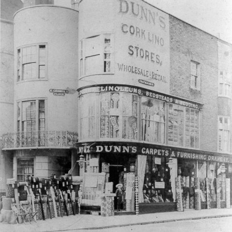 Dunn's Carpets and Furnishing Drapery, c. 1900: Dunn's Carpets and Furnishing Drapery was at 17 St George's Place, at the corner with Trafalgar Street from the 1880s onwards. Rolled carpets, linoleum and rugs can be seen standing on the pavement and in a first floor display window, a common feature designed to catch the eye of potential customers travelling on the upper deck of a tram. St George's Place is a short terrace of bow-fronted houses built in the 1820s, possibly by Wilds and Busby. | Image reproduced with kind permission from Brighton and Hove in Pictures by Brighton and Hove City Council