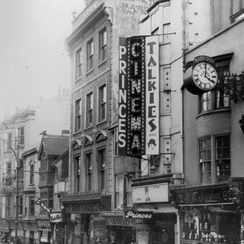 Princes Cinema, 1933: The Prince's Cinema in North Street following the introduction of a new foyer and a neon lit facade. A cinema first opened on this site in 1911, known as the Bijou Electric Empire. Following 7 name changes, including a spell as Brighton Film Theatre from 1969 to 1978, it closed as the Cinescene in 1983. It has now been refurbished as a fast-food restaurant. | Image reproduced with kind permission from Brighton and Hove in Pictures by Brighton and Hove City Council