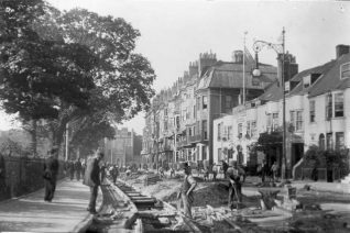 Workmen laying tram rails in Marlborough Place, opposite the King and Queen public house. The tram service began along this route on 25 November 1901, although the network was not completed until 1904. The bow-fronted Georgian King and Queen was replaced by the current red-brick timber-framed building in 1931-32. | Image reproduced with kind permission from Brighton and Hove in Pictures by Brighton and Hove City Council