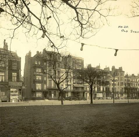 Old Steine looking East, 1930s: Buildings on the East side of the Old Steine. A string of electric light bulbs dangles overhead amongst the trees. Amongst the row of hotels and hostels is the Regal Safety Coaches booking office, where London could be reached for 4 shillings. | Image reproduced with kind permission from Brighton and Hove in Pictures by Brighton and Hove City Council