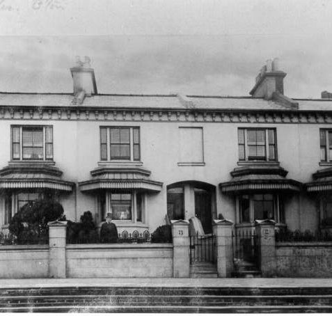 Clifton Terrace, 1870s: Clifton Terrace was completed in 1847 in late Regency style, with bonnet-like canopies above angular bay windows. A boy in a top hat stands in the garden of No. 3, while 3 adults and a small dog can be seen in the ground floor window. Opposite the terrace there was a private garden for residents' use. | Image reproduced with kind permission from Brighton and Hove in Pictures by Brighton and Hove City Council