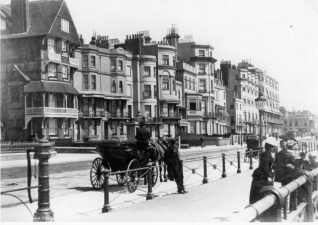 Marine Parade, c. 1890s: Marine Parade was developed east of the Steine from the 1790s. Many of the houses were refronted by Charles Busby and A. H. Wilds in the 1820s. After the promenade had been developed in 1827-38, the seafront area between Kemp Town and Brunswick Town became a fashionable carriage drive. The building on the left is now the Lanes Hotel. With white windows and verandas against a red-brick and flint background, it was remodelled and refronted in a Queen Anne style in 1880 by Colonel Robert Edis of the Artists' Rifles. | Image reproduced with kind permission from Brighton and Hove in Pictures by Brighton and Hove City Council