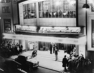 People queuing outside the Regent Cinema. Above the entrance the restaurant can be seen. A banner advertises that Tyrone Power is appearing in the film Seven Waves Away. At this time, there was ballroom dancing was evening with music by the Syd Dean Orchestra. | Image reproduced with kind permission from Brighton and Hove in Pictures by Brighton and Hove City Council