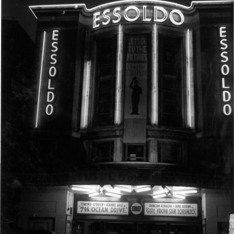 Illuminated facade of Essoldo Cinema, c. 1950s: Opening as the 2000 seater Imperial Theatre in 1940, the last traditional theatre to be built in Brighton, it was renamed the Essoldo in 1949 and operated as a cinema until May 1964 when it became a bingo club. The building was used as a bar complex in the late 1990s but is currently closed. This photograph shows the facade illuminated by neon tubes at night. A banner hanging between two vertical neon strips advertises Charlie Chaplin's