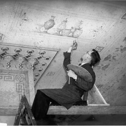 A conservator is retouching some of the detail of a ceiling in the Royal Pavilion. The first programme of restoration began in October 1920 following the return of the Royal Pavilion estate to Brighton Corporation following almost six years of use as a military hospital. | Image reproduced with kind permission from Brighton and Hove in Pictures by Brighton and Hove City Council