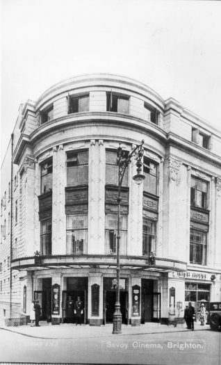 Corner Side Entrance of Savoy Cinema, 1930: The Savoy Cinema opened on 1 August 1930 on the site of Brill's Baths in Pool Valley. Two uniformed doormen can be seen at the doors of the corner entrance in East Street to the cinema. From 1963 it has been known as the ABC cinema. In 1975-76 the cinema was converted into 4 smaller screens, the largest of which has been disused for several years. In 1999-2000 the cinema was due to be converted into a casino, bar and restaurant development. | Image reproduced with kind permission from Brighton and Hove in Pictures by Brighton and Hove City Council
