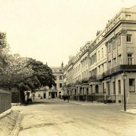Houses in Sussex Square, c. 1935: Facades of houses on the East side of Sussex Square. Sussex Square was built between 1823-1827 by Amon Wilds and designed by Charles Busby as part of the Kemp Town estate. All of the houses have Doric or Ionic porches and ironwork balconies and every third house has pilasters, most of which have Corinthian capitals. | Image reproduced with kind permission from Brighton and Hove in Pictures by Brighton and Hove City Council