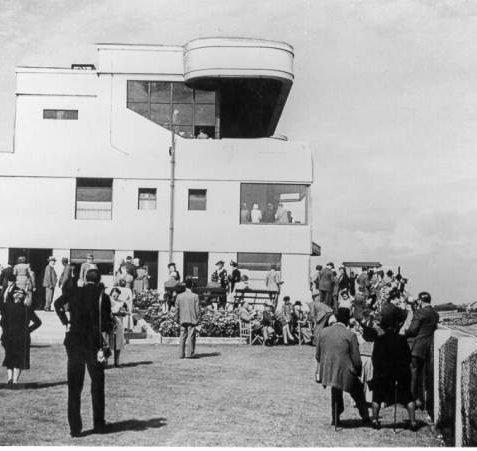 Club Stand at Brighton Racecourse, 1946: Group of spectators gathered outside the Club Stand of Brighton Racecourse. The Club Stand was built in 1936 by Yates, Cook and Derbyshire of London in Art Deco style. It was demolished in 1965 after the current grandstand opened. | Image reproduced with kind permission from Brighton and Hove in Pictures by Brighton and Hove City Council