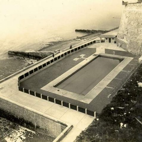 Rottingdean Swimming Pool, c. 1935: Aerial view of Rottingdean Swimming Pool. This opened on 29 July 1935 to replace bathing facilities lost when the sea wall and Under cliff walk were built. It was a seawater pool and measured 100 feet by 35 feet. It was filled in with concrete in 1994. | Image reproduced with kind permission from Brighton and Hove in Pictures by Brighton and Hove City Council