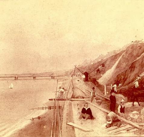 Construction of Esplanade at East Cliff, c. 1830-33: Brighton's East Cliff rises to about 80 feet above the sea at Eaton Place. In 1830 to 1833 a cement sea wall was built along the face of the East Cliff between Old Steine and Royal Crescent. A large amount of rubble was then tipped over the edge of the cliff top to further protect the wall. An esplanade, or carriage road, was then built on top of this sea wall. | Image reproduced with kind permission from Brighton and Hove in Pictures by Brighton and Hove City Council