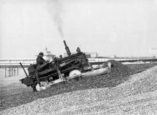 Moving Shingle on Brighton Beach, 1950: Shingle is being shifted by bulldozer on Brighton Beach. Embassy Court can be seen on the right beyond the West Pier. | Image reproduced with kind permission from Brighton and Hove in Pictures by Brighton and Hove City Council