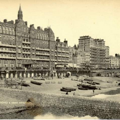 Brighton Metropole and Grand Hotels, c. 1905: A view of Brighton Beach in front of the Hotel Metropole and the Grand Hotel on King's Road. Fishing and pleasure boats are on the beach, as are a few fully-clothed people sitting on wooden benches. Above bathing huts, people can be seen promenading along King's Road, on foot and in carriages   Image reproduced with kind permission from Brighton and Hove in Pictures by Brighton and Hove City Council