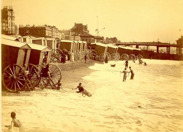 Bathing Machines at the West Pier, c1885. Young women bathing in the sea from bathing machines near to the West Pier, holding onto ropes in case they are swept out to sea. The Hotel Metropole had not yet dominated the skyline along this portion of coastline. The towers of the Chain Pier can be seen in the distance. | Image reproduced with permission from Brighton History Centre