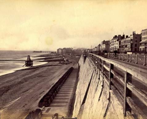 Seafront East of Chain Pier looking West, c. 1875: Seafront east of Chain Pier looking West. The sea wall on the right was built in 1827-38, with a promenade running along the top alongside the road on Marine Parade. In 1880 these wooden railings were replaced by the present cast-iron railings with dolphin motifs. | Image reproduced with kind permission from Brighton and Hove in Pictures by Brighton and Hove City Council