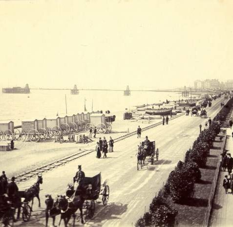 Seafront looking West from Kemp Town, c. 1895. A view of the seafront looking west from Kemp Town towards the Chain Pier. The Volk's Electric Railway track can be seen running along the beach, on which there are numerous boats and bathing machines. People can be seen promenading along a pathway now covered by the arched Madeira Terrace. | Image reproduced with kind permission from Brighton and Hove in Pictures by Brighton and Hove City Council